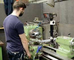 An apprentice is machining a feed bushing on a conventional lathe